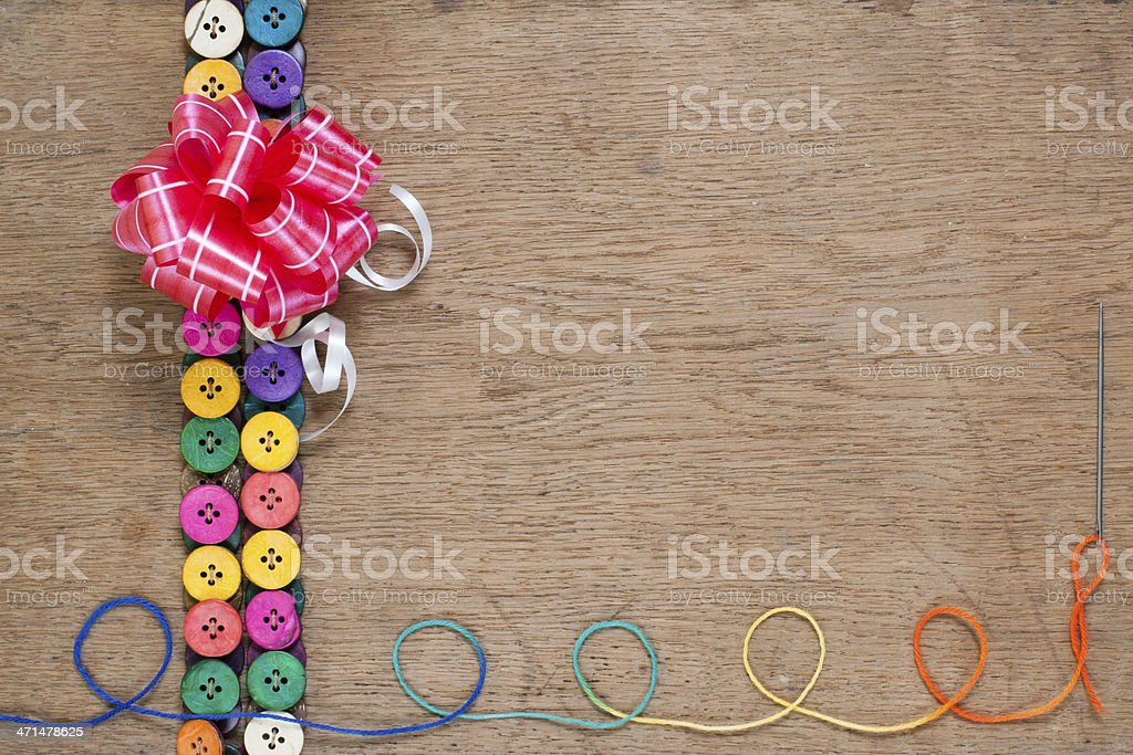 Gift bow, colorful buttons, thread with needle on wood royalty-free stock photo