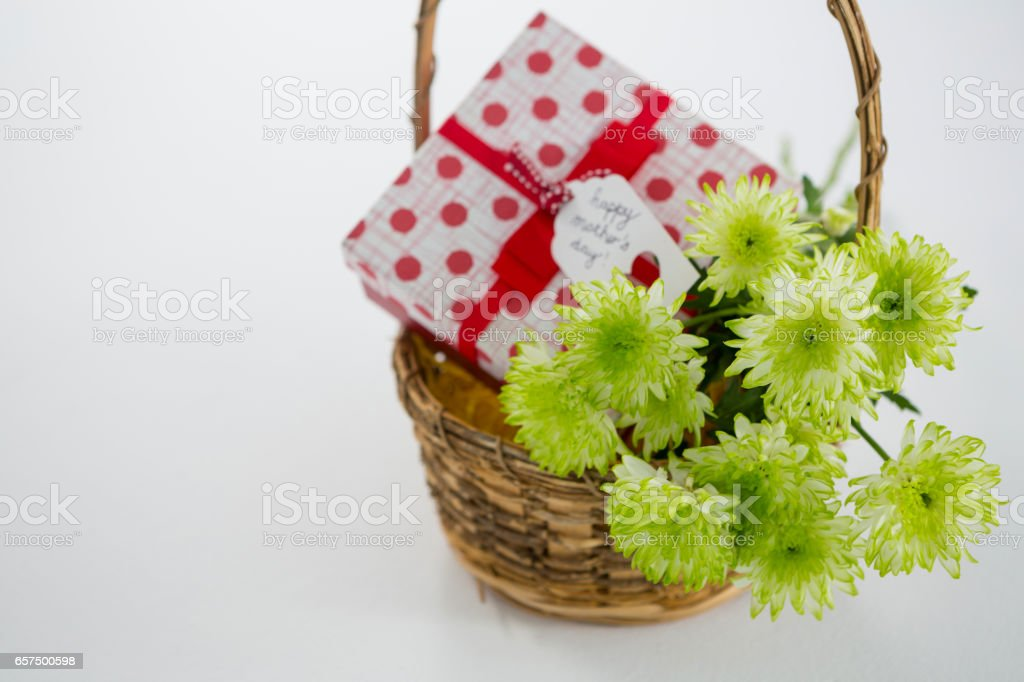 Gift box and bunch of yellow flowers in wicker basket with happy mothers day tag stock photo