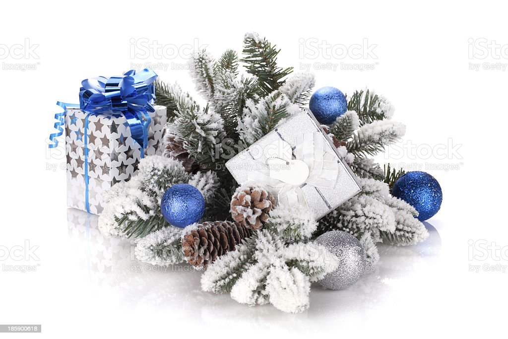 Gift box and christmas decor on snowy fir tree royalty-free stock photo