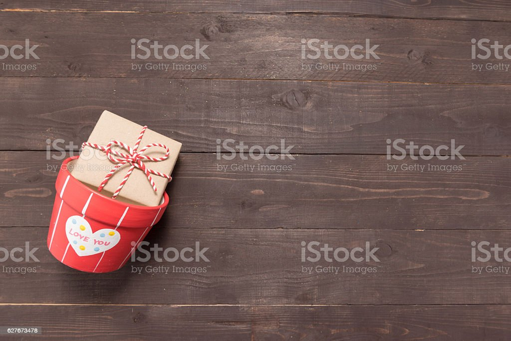 Gift box and flower pot are on the wooden background stock photo
