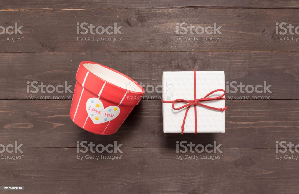 Gift box and flower pot are on the wooden background with empty space stock photo