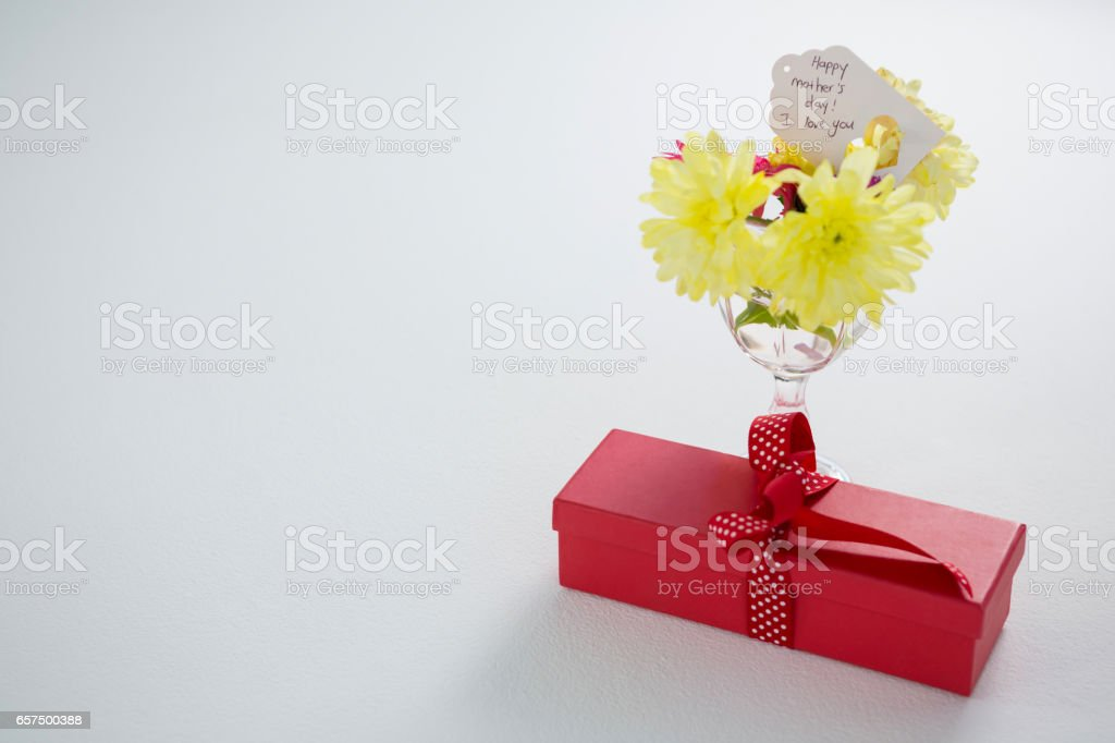 Gift box and flowers in glass with happy mothers day tag stock photo