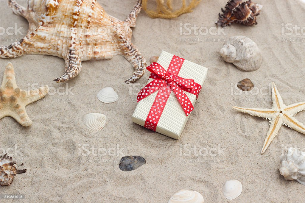 Gift box and net with shells on sand stock photo