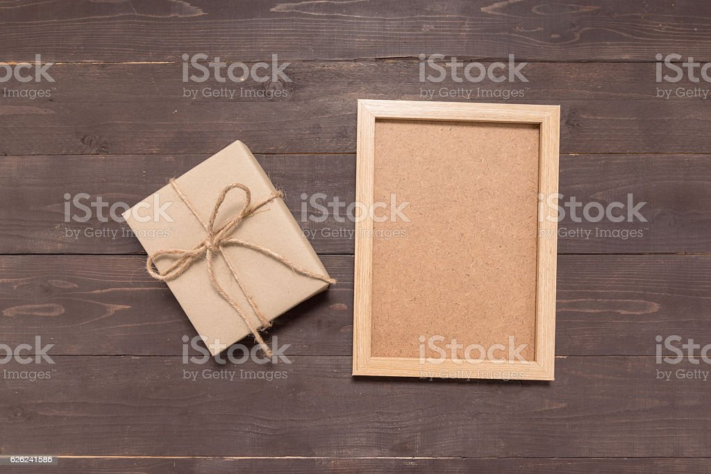 Gift box and picture frame are on the wooden background stock photo