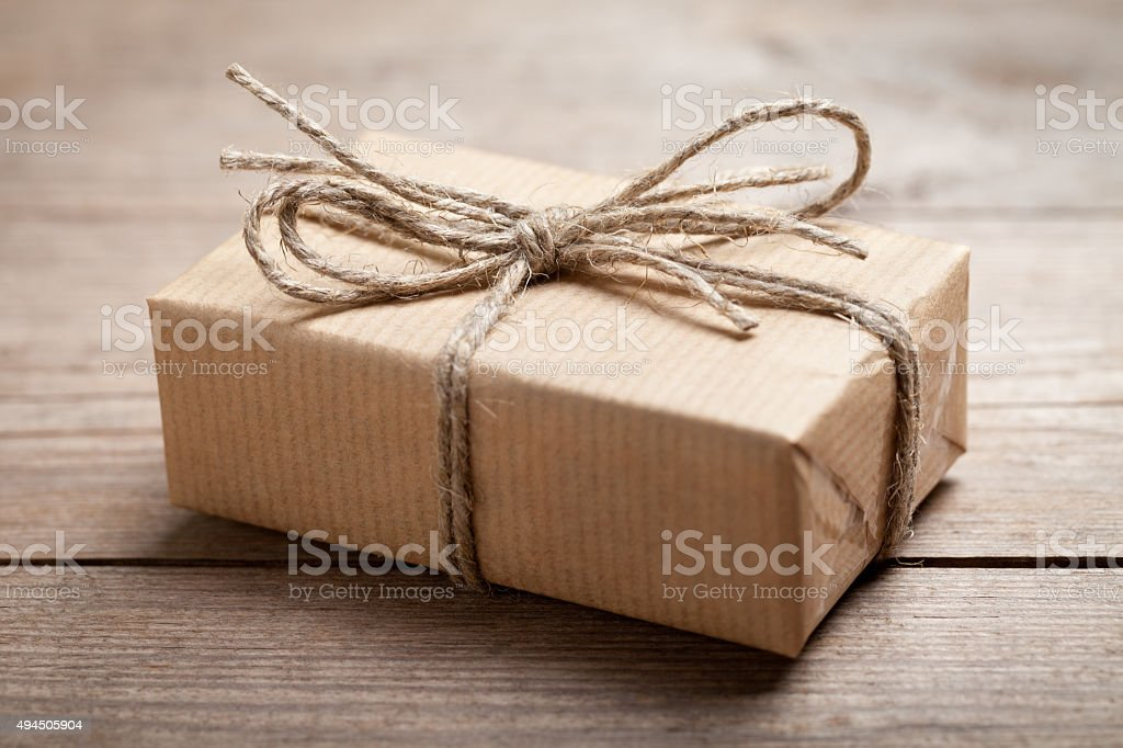 Gift box in recycled paper on old table stock photo