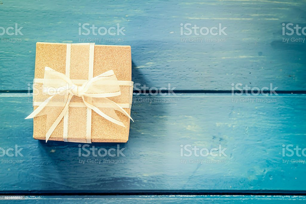 Gift box on blue wooden table,vintage filter stock photo