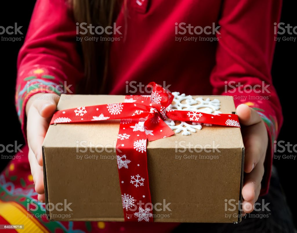 Gift box tied with a red ribbon in the hands stock photo