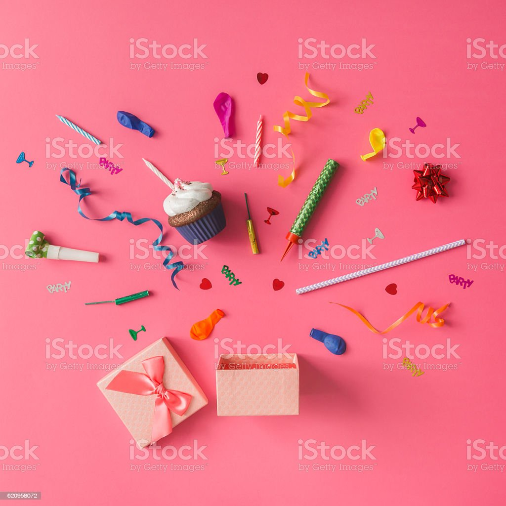 Gift box with colorful party items on pink background. stock photo
