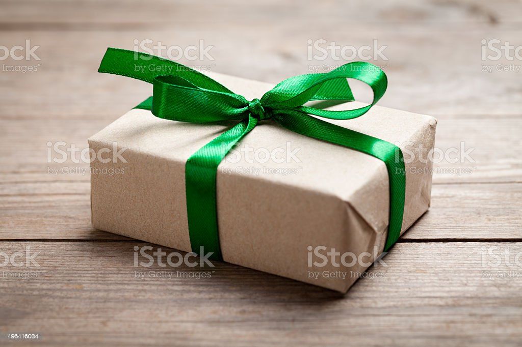 Gift box with green ribbon on wooden table stock photo