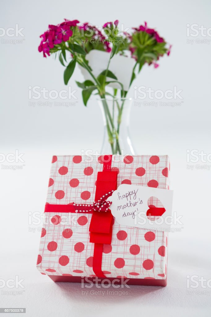 Gift box with happy mothers day tag and flower vase stock photo