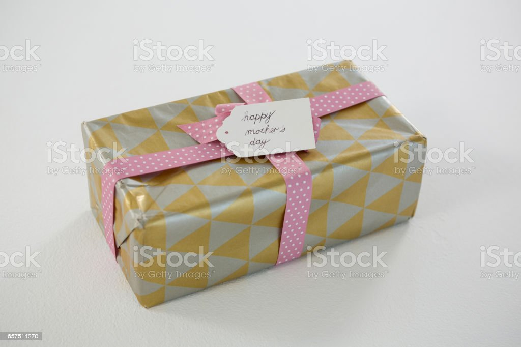 Gift box with happy mothers day tag on white background stock photo