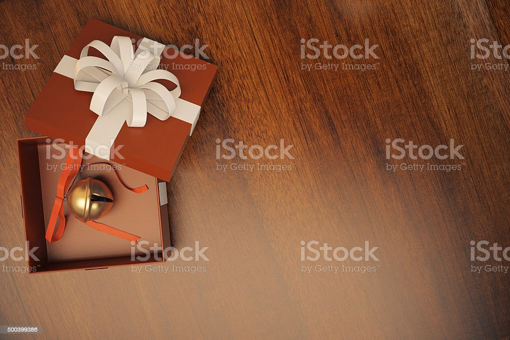 Gift box with jingle bell on wooden floor stock photo