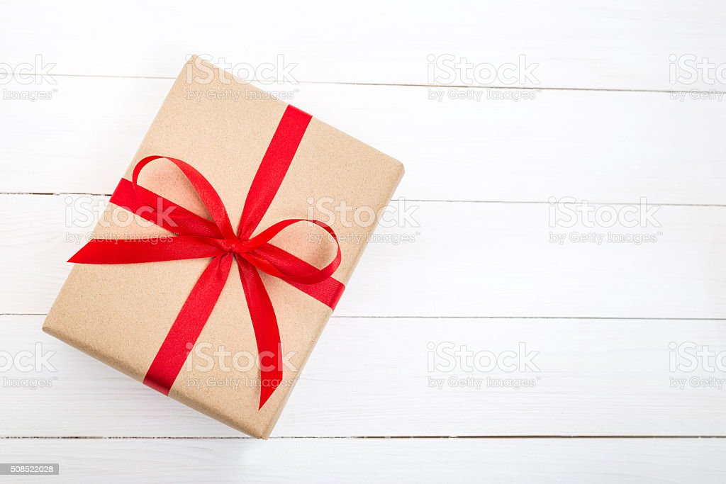 Gift box with red ribbon bow on white wooden background stock photo