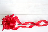 Gift box with red ribbon bow on wooden white background