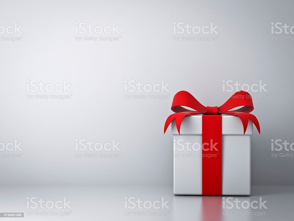 Gift box with red ribbon bow with empty white wall stock photo