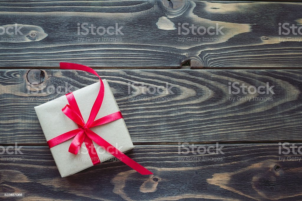 Gift box with red ribbon on the wooden table stock photo