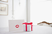 Gift box with ribbon and card with lipstick kiss on desk