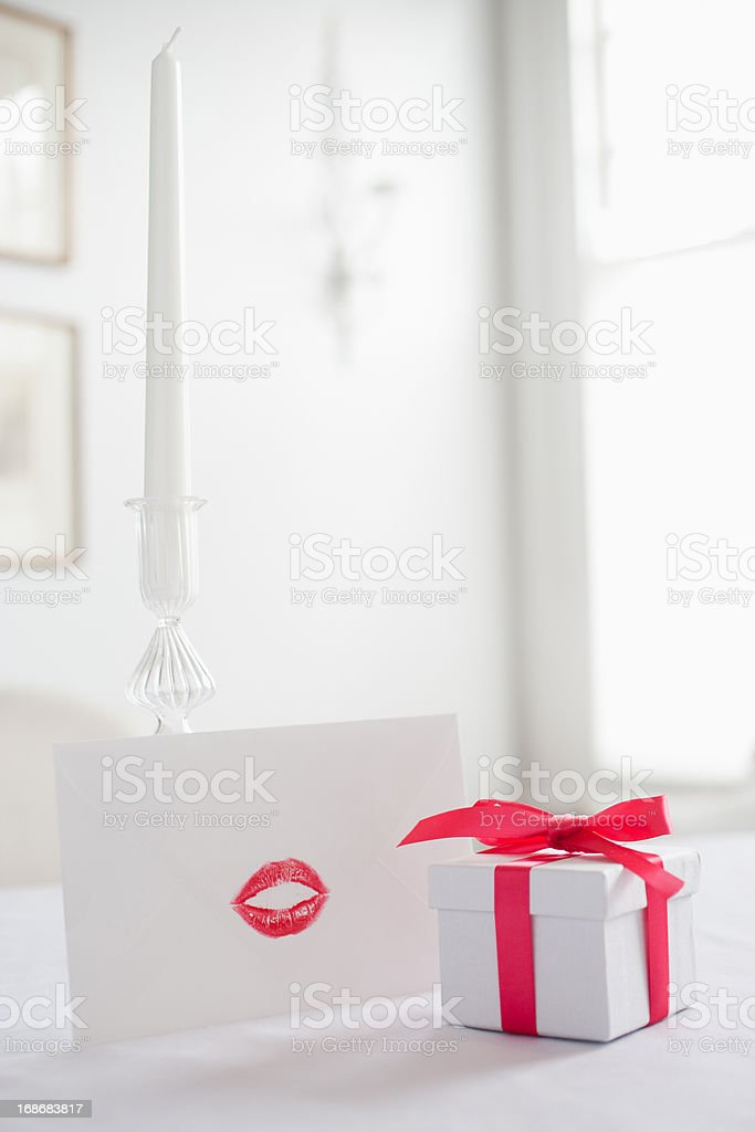 Gift box with ribbon and card with lipstick kiss on desk royalty-free stock photo