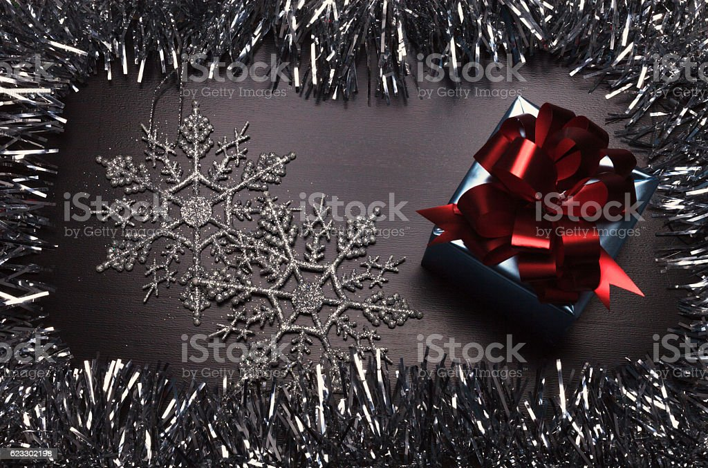 Gift box with snowflakes on wooden background stock photo