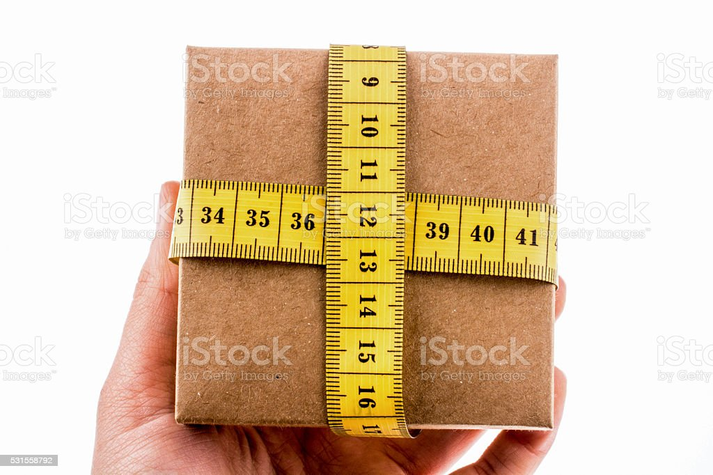Gift box wrapped with  tape measure stock photo