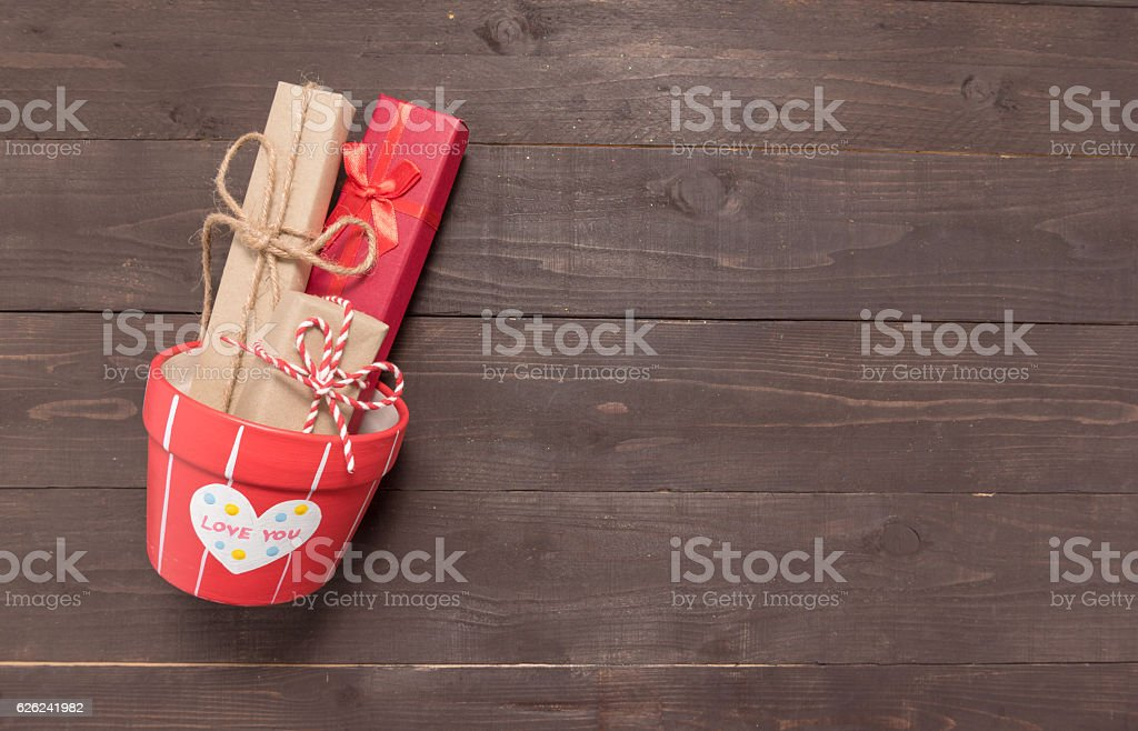 Gift boxes and flower pot are on the wooden background stock photo