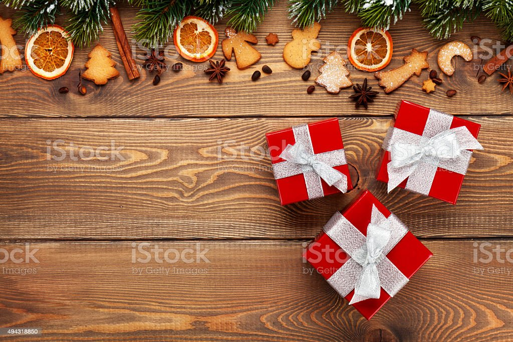 Gift boxes over christmas wooden background stock photo