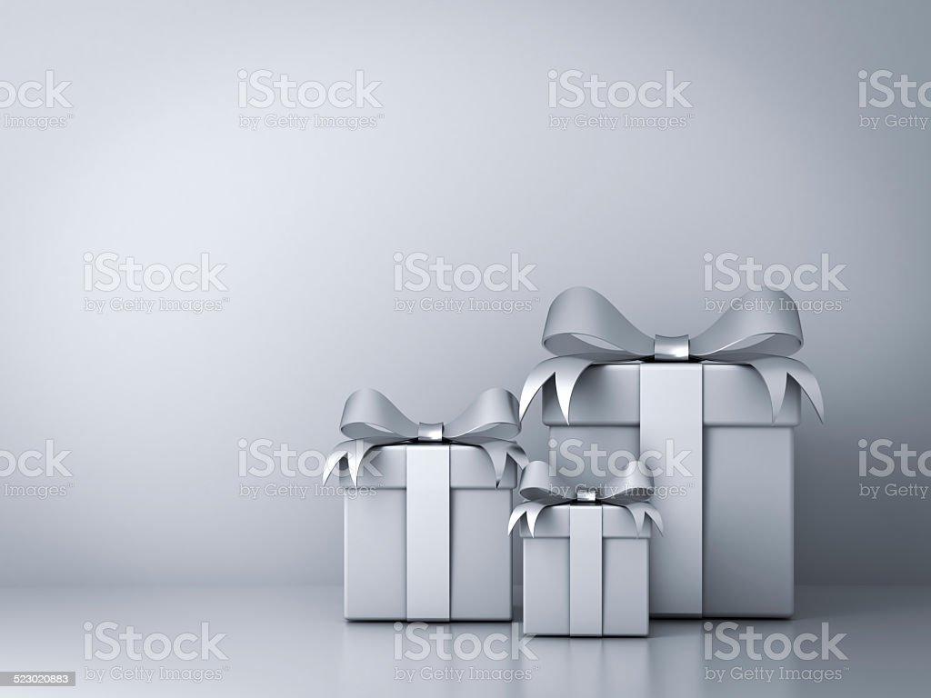 Gift boxes with silver ribbon bow and empty white wall stock photo