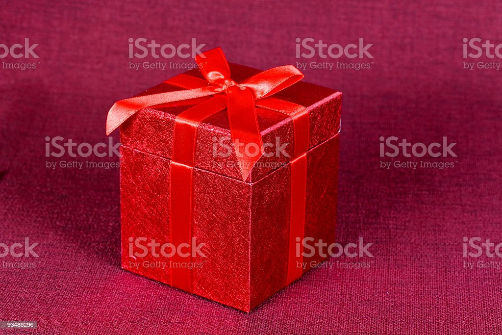 gift box,with red ribbon, on  textile background royalty-free stock photo