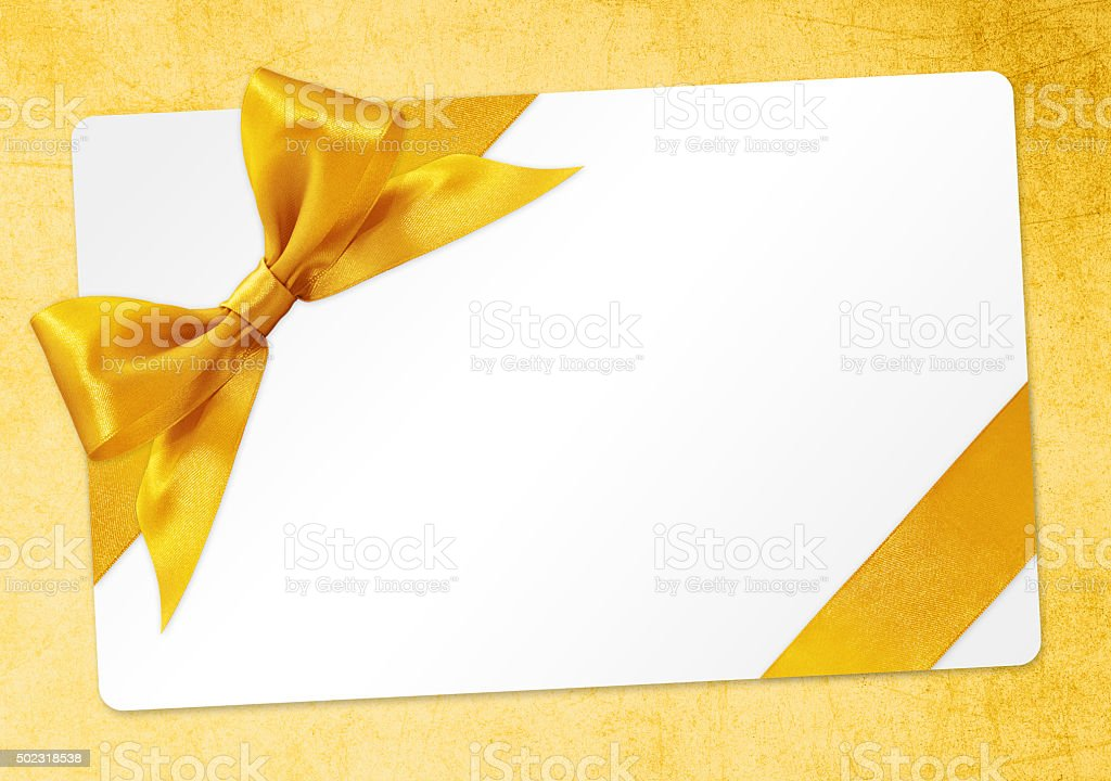 gift card with golden ribbon bow Isolated on yellow background stock photo