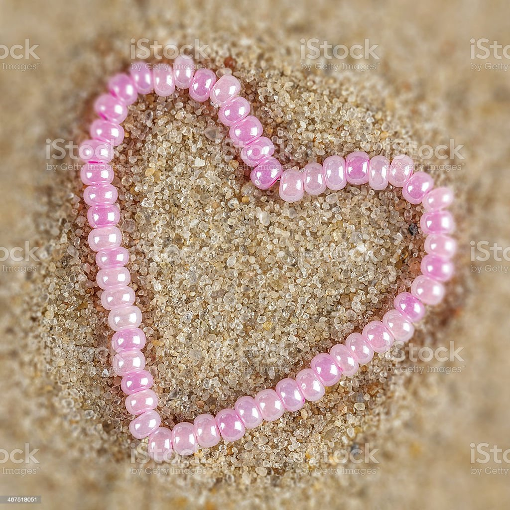 Gift heart shaped beads on a background of sand. royalty-free stock photo
