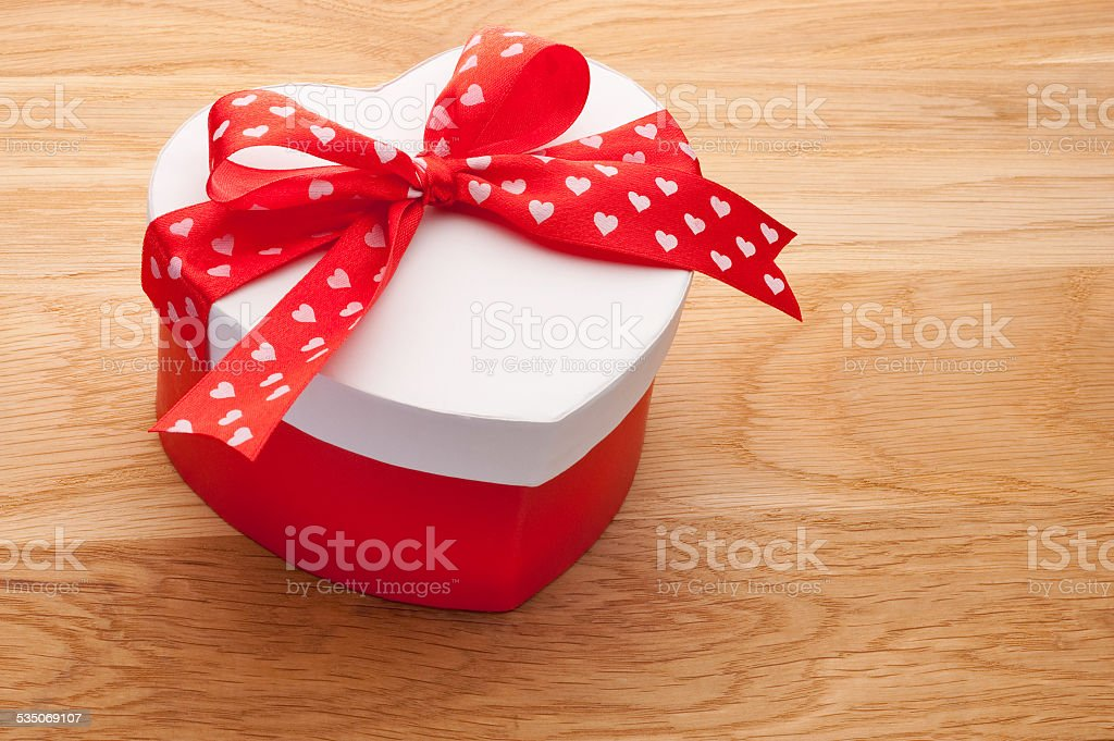 Gift in the form of heart tied with red ribbon stock photo
