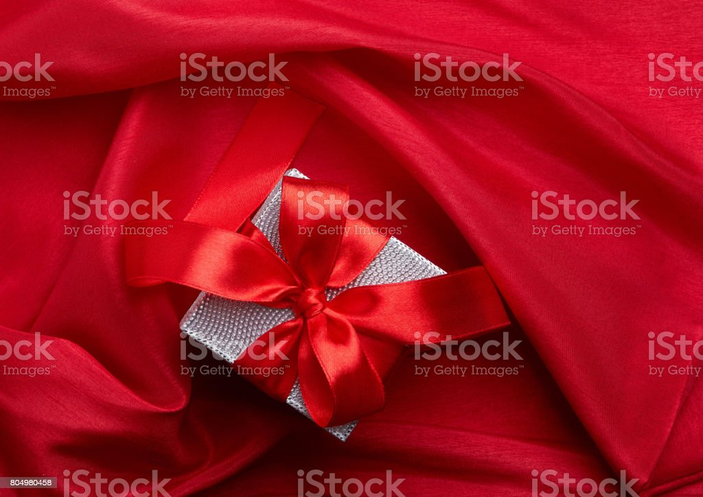 Gift on red fabric stock photo
