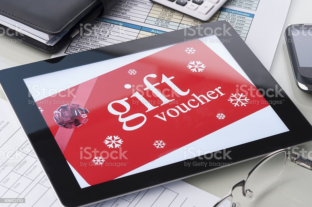 Gift voucher on a digital tablet with bow