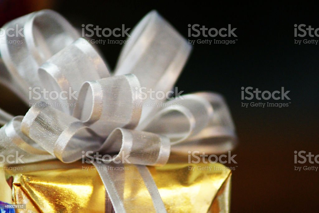 Gift with Gold Wrapping Paper and Silver Bow stock photo
