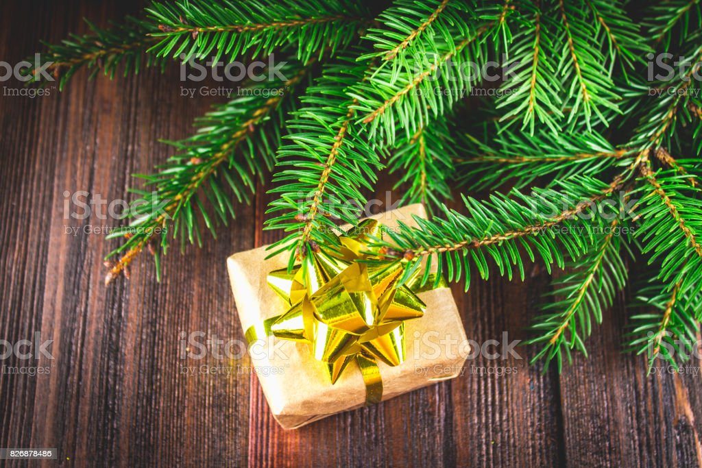 gift with golden bow under the Christmas tree branches on a wood stock photo