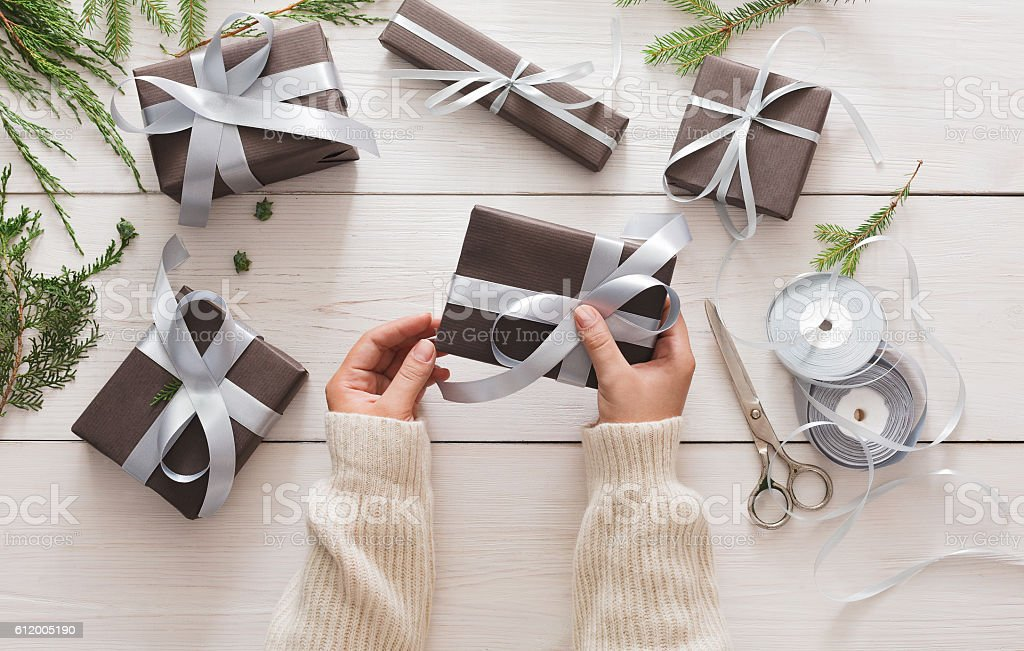 Gift wrapping. Packaging modern christmas present in boxes stock photo