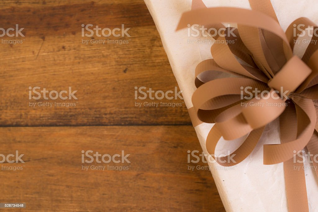 Gifts:  Wrapped gift.  White box with brown bow. stock photo