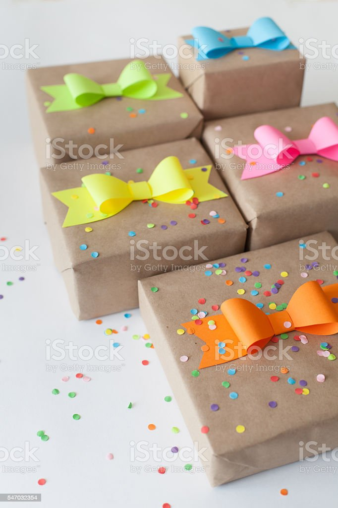 Gifts wrapped in kraft paper. Coloured bright paper bows. stock photo