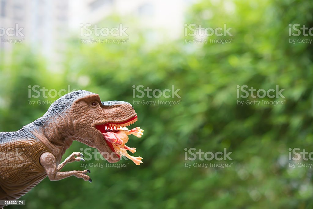 gigantic tyrannosaurus catches a smaller dinosaur in front of trees stock photo