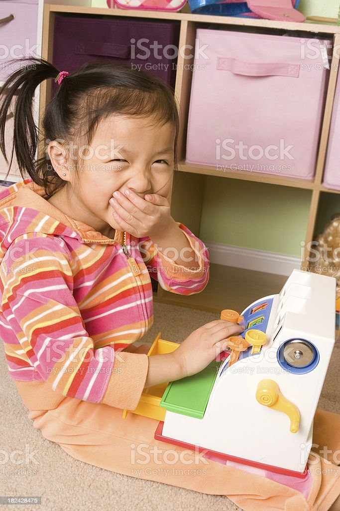 Giggling girl playing with cash register royalty-free stock photo