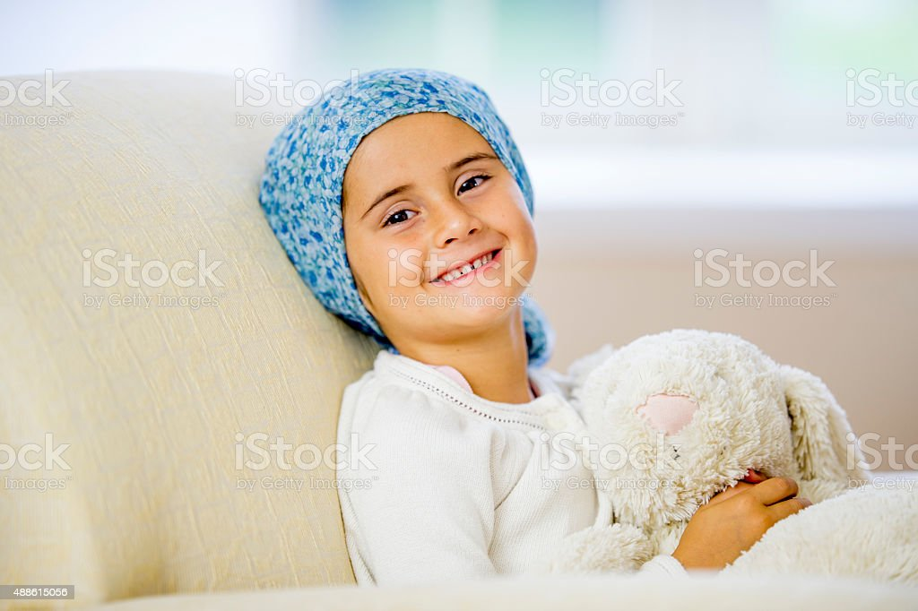 Giggling Little Girl Facing Cancer stock photo