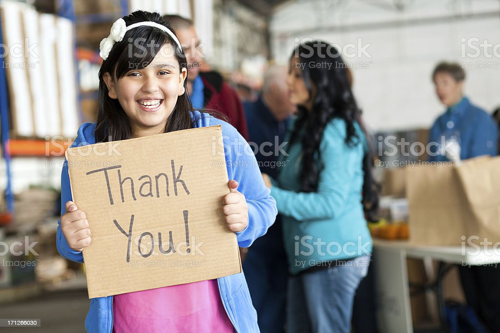 Giggling young girl holding Thank You sign at donation center royalty-free stock photo