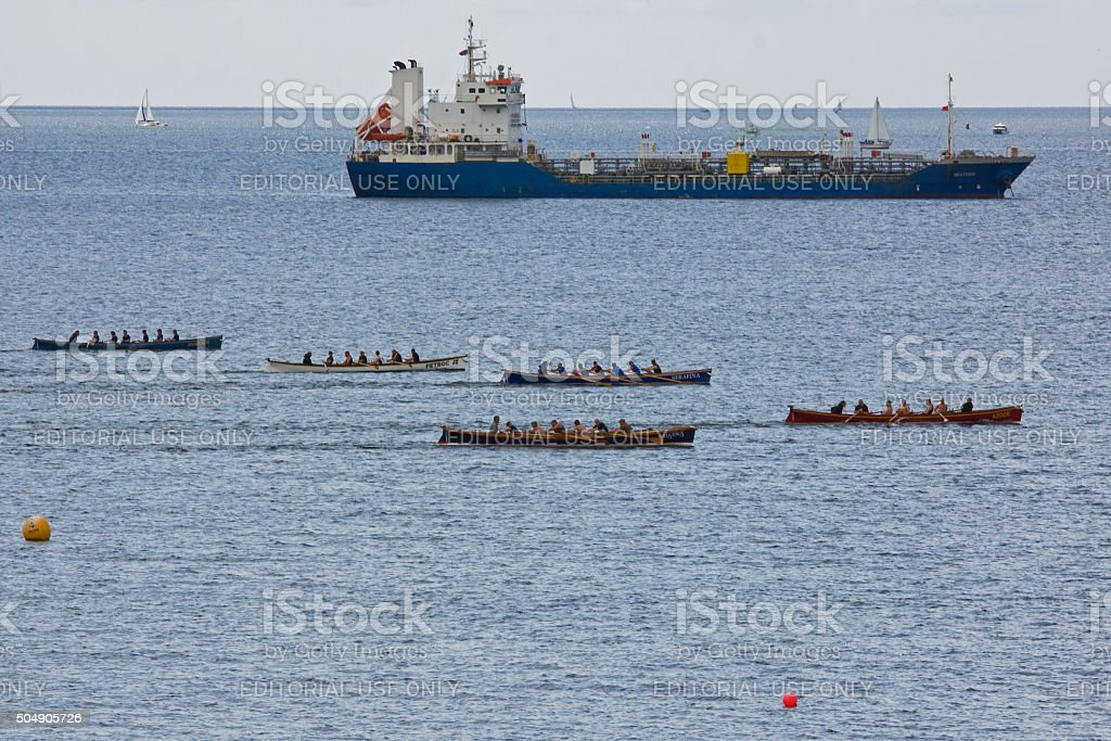 Gigs racing alongside a cargo boat in Falmouth harbour UK stock photo