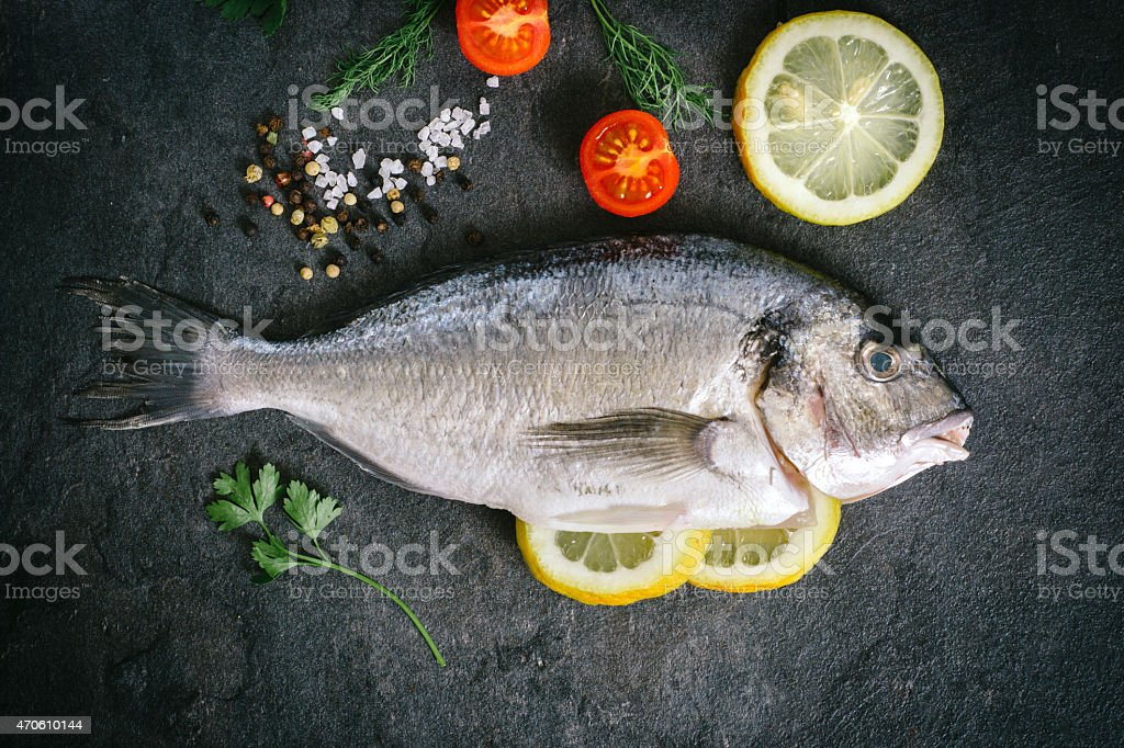 Gilthead fish on dark board stock photo