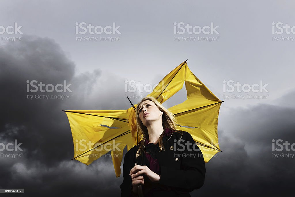 Gimme shelter! Sad blonde with broken umbrella in thunderstorm royalty-free stock photo