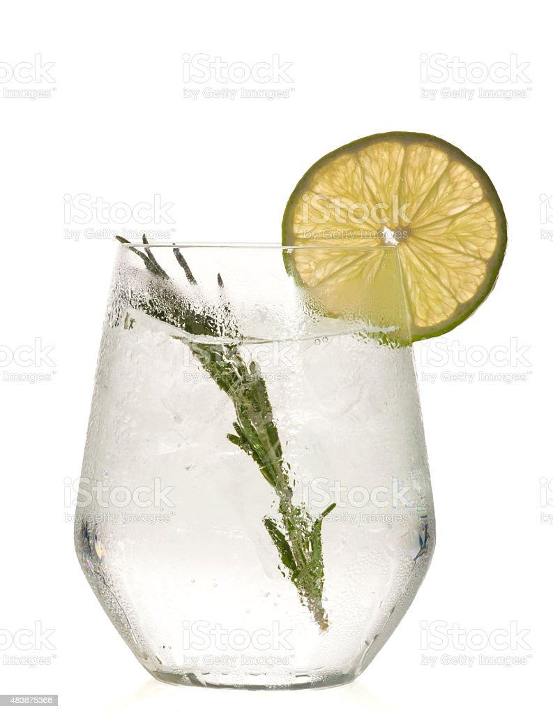 Gin and tonic cocktail with lime over white background. stock photo