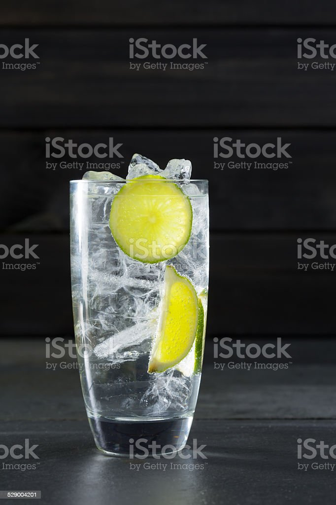 Gin tonic cocktail with lima and ice cube on black stock photo