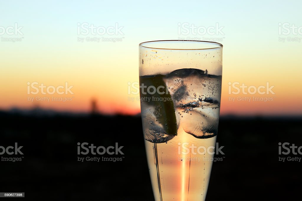 Gin tonic with ice cubes lit by sun during sunset stock photo