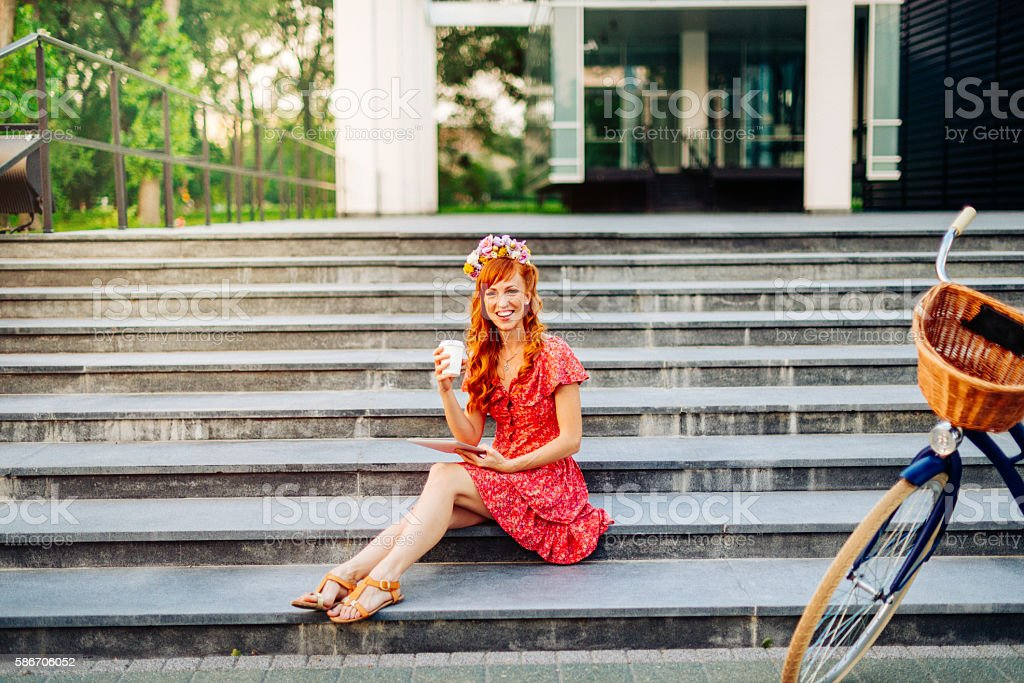 Ginger drinking coffee and updates social network profile stock photo