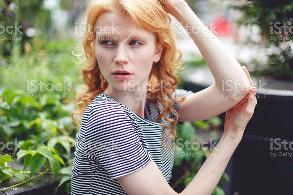 Ginger girl in green bush on street, photo toned stock photo